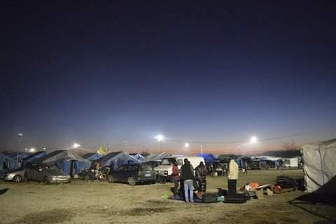 In this photo taken on Monday, Feb. 1, 2016, people stand by the tent city of San Ferdinando, Southern Italy, where about 1,200 migrants and refugees live without access to basic services. Thousands of migrants, many from Africa, who harvest oranges in the southern Italian region of Calabria during the fruit-picking season, live on meager wages and in squalid conditions, some in abandoned farmhouses or derelict factories, often with no running water or electricity. (ANSA/AP Photo/Annalisa Camilli)